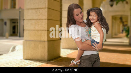 Outside the shopping center a mother bonds with her happy young daughter holding her close in her arms as she enjoys the child's smile. - Stock Photo