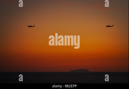 Two helicopters flying in southern California against the setting sun. - Stock Photo
