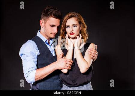 Young man comforting crying sad woman in the studio - Stock Photo