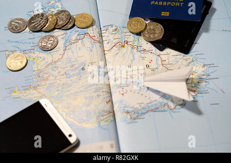 Coins of Iceland, the plane, smartphone, biometric passport, dollars, coins and credit cards lie on a map of Iceland - Stock Photo