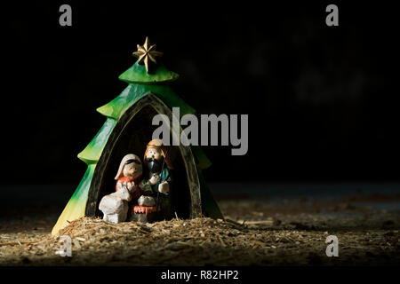 the holy family, the child jesus, the virgin mary and saint joseph, in a rustic nativity scene against a dark background with some blank space on the  - Stock Photo