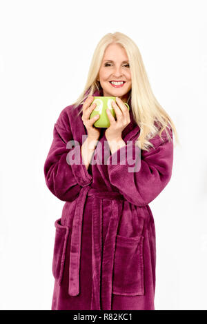 Attractive woman in purple fluffy dressing gown holding hands around a mug of tea, taken against white background - Stock Photo