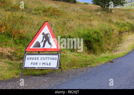 UK Triangle road sign warning of grass cutting for one mile - Stock Photo