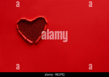 Ripped paper hole heart shaped on red paper background. Valentine's day celebration concept - Stock Photo