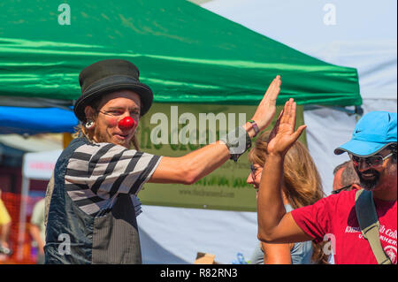 Portland, Oregon,USA - August 17,2014:  Hawthorn Street annual Community Event.  A clown high fives a man who has been watching him perform. - Stock Photo