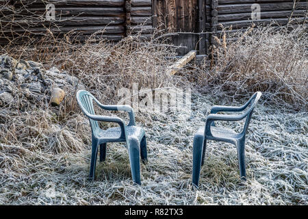 Two blue plastic chairs with frozen rime in a rural garden with rustic farm house and grass covered in ice cold hoar frost an early winter morning - Stock Photo