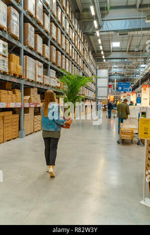 Warehouse storage inside IKEA store.IKEA is the world's largest furniture retailer. Young girl carrying a plant. - Stock Photo