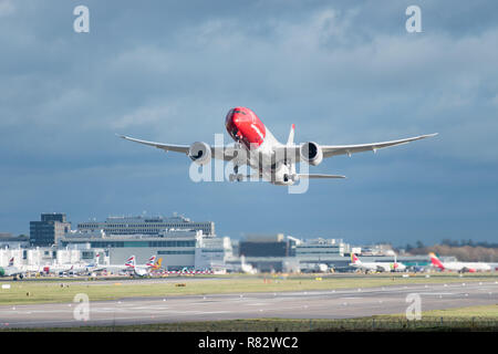 GATWICK AIRPORT, ENGLAND, UK – DECEMBER 09 2018: A Norwegian Airlines plane takes off from London Gatwick Airport, with jet wash wake turbulence - Stock Photo