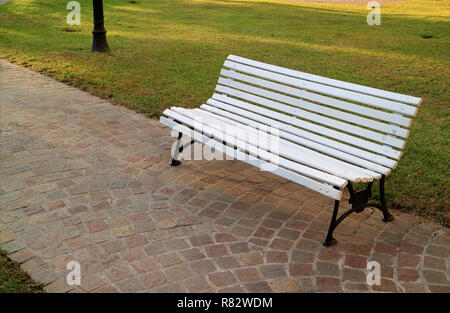 White Colored Wooden Bench on Stone Paved way in the Public Garden, Buenos Aires of Argentina - Stock Photo