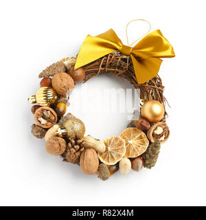 Beautiful Christmas wreath consisting of dried orange slices, nuts, cones, decorated with a large yellow bow on a white background - Stock Photo