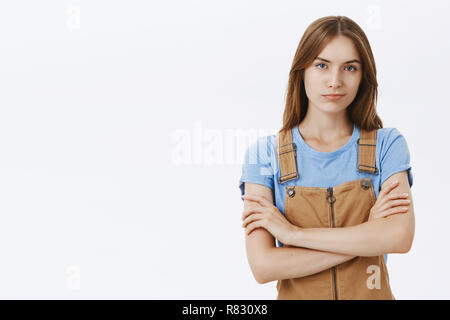 Waist-up shot of confident good-looking woman with good self-esteem holding hands crossed on chest in proud self-assured pose smirking as if being skillful and smart posing arrogant over gray wall - Stock Photo