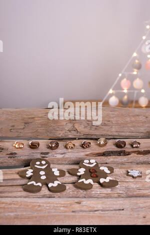 Gingerbread men lie with bronze colored Christmas tree pendants on old wooden beams. - Stock Photo