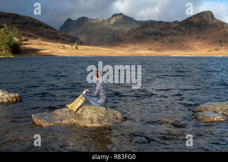 Woman sitting on a rock in Blea Tarn admiring the landscape which includes the Langdale Hills, Cumbria, UK. - Stock Photo