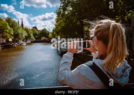 Rear view of female tourist taking photo of canal in Amsterdam on the mobile phone on sunny autumn day. Warm gold afternoon sunlight. Travel in Europe - Stock Photo
