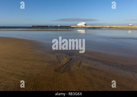 Matosinhos peaceful beach at low tide on a bright morning with interesting sand structures in the foreground and the south of Leixoes harbor in backgr - Stock Photo
