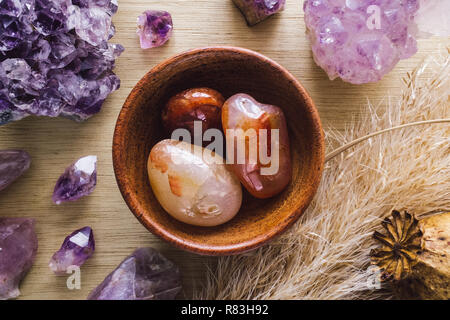 Teak Bowl of Carnelian with Amethyst Crystals and Dried Poppy Flower on Wood Table - Stock Photo