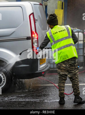 One man using Water Jet Spray to hand wash a vehicle in Rotherham, South Yorkshire, England - Stock Photo