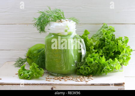 Green smoothie with kiwi, spinach, cucumber and orange - Stock Photo