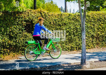 August 26, 2018 Mountain View / CA / USA - Girl riding a Lime bike on a sidewalk in Silicon Valley; Lime is an American transportation rental company  - Stock Photo