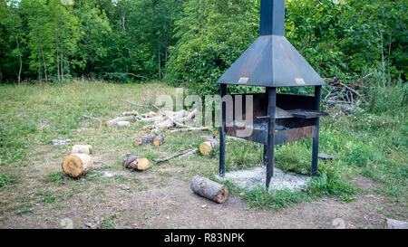 A great little picnic area in the forest with a grill and a fire ring plus its all under a nice shade summer house - Stock Photo