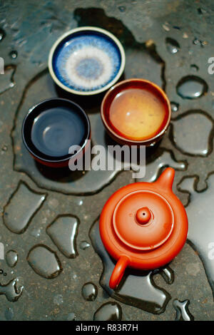 Brewing tea in chinese way (gon fu) with clay pot on surface covered by raindrops - Stock Photo