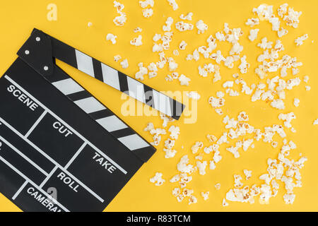top view of cinema clapperboard and crunchy popcorn isolated on yellow - Stock Photo