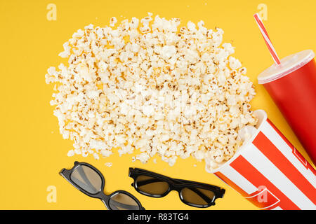top view of 3d glasses, red disposable cup with straw and overturned striped bucket with popcorn isolated on yellow - Stock Photo