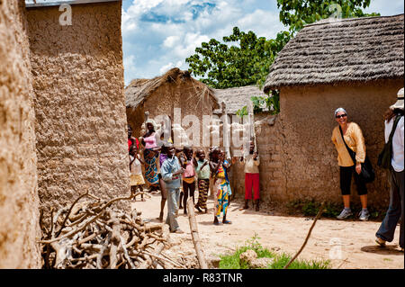 Mali, Africa. White caucasian volunteers  and black african people enjoy life in a rural village near Bamako. - Stock Photo