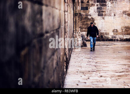 Man walking down an alley in Gothic Quarter in Barcelona - Stock Photo