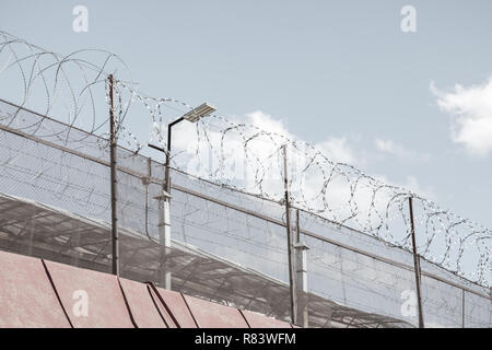 Prison fence with barbed wire. - Stock Photo