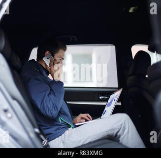 business man uses a laptop and mobile phone sitting in the car - Stock Photo