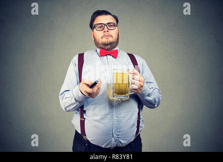Adult lazy obese man in formal outfit holding mug of beer and watching TV on gray background - Stock Photo