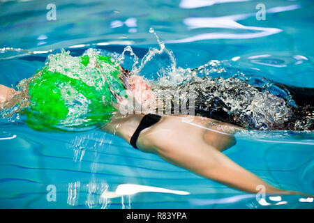 oung man swimmer with green cap swims front crawl or forward crawl stroke in a swimming pool for competition or race - Stock Photo