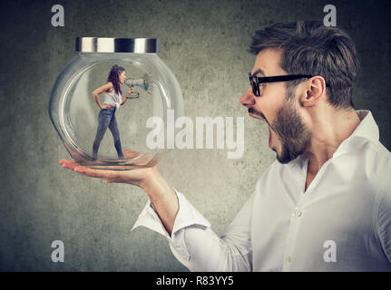 Frustrated businessman holding a glass jar with an angry screaming woman trapped in it - Stock Photo