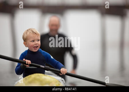 Young boy sticks his tongue out in concentration as he tries to row a kayak while his father helps to push it along in the waters of a foggy harbour. - Stock Photo