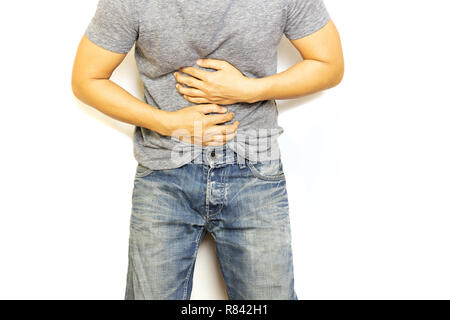 Man with stomach pain hand holding his aching belly isolated. - Stock Photo