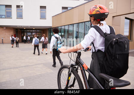Group Of High School Students Wearing Uniform Arriving At School Walking Or Riding Bikes - Stock Photo