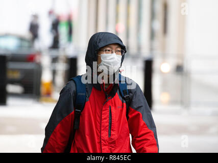 A Japanese tourist in London wearing an Air-pollution face mask to combat the toxins and pollution in the air - Stock Photo