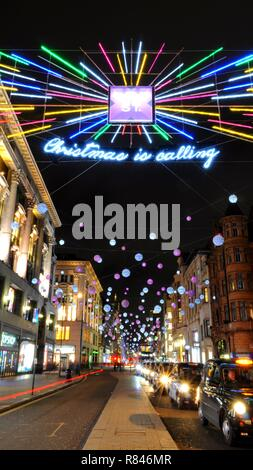 Black Cabs under 2018 Christmas lights along Oxford Street Toward Oxford Circus, Soho, London, UK. - Stock Photo