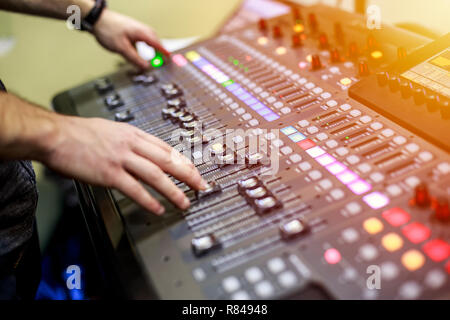 Person adjusting audio mixing console on music studio. Buttons of audio sound mixer board. - Stock Photo