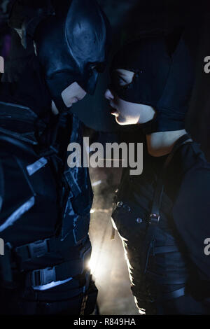 A man dressed as a bat and a woman dressed as a cat stand next to each other on background of light. Cosplay. Closeup. - Stock Photo
