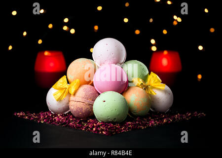 Pyramid of colorful bath bombs on the dark background surrounded by dried rose petals, candles and light in the background - Stock Photo