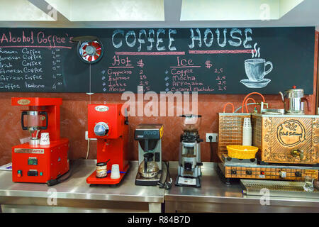 Bar in the hotel, coffee machines for grinding and preparing a fresh, aromatic drink. Prices are written in chalk on a special blackboard on the wall. - Stock Photo