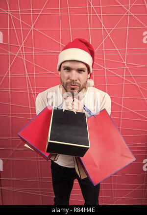 Winter sale, shopping concept. Santa shopper with paperbags on pink background. Christmas and new year presents. Man in xmas hat hold colorful bags. Holidays preparation and celebration. - Stock Photo