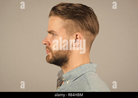 Man with bearded face in profile. Macho with beard and mustache. Guy with stylish hair and unshaven skin. Beard grooming and hair care in barbershop. Skincare and mens beauty concept. - Stock Photo