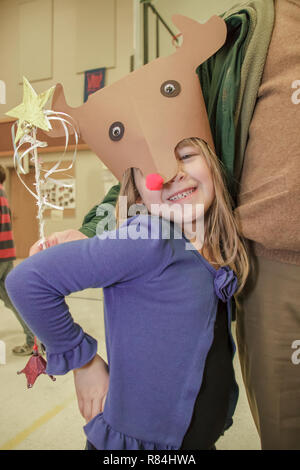 Six year old girl showing off her handmade Rudolf hat at a school crafts fair standing by her Grandpa.  (MR) - Stock Photo