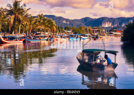 A local fisherman goes out on a boat from boats park to the sea for fishing. Traditional colorful asian fishing boats in fishing village. Langkawi. - Stock Photo