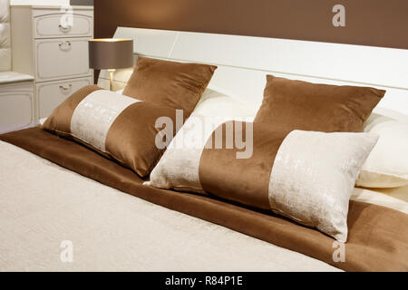 luxury modern style bedroom in brown and beige tones, Interior of a hotel bedroom, cushions with a pattern ornament - Stock Photo