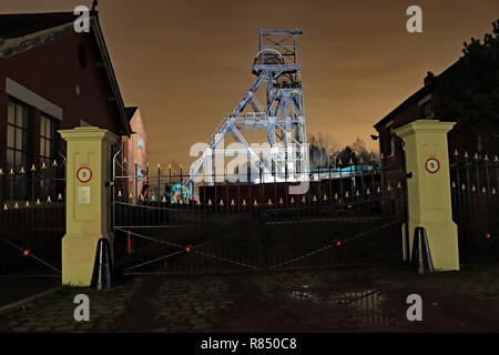 Lit pit head gear and entrance gate to Astley colliery 11.12.18  The pit head gear at the Astley Mining museum lit up for a few weeks over Christmas - Stock Photo