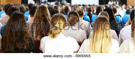 wide shot of a large number of high school students in mixed uniforms facing the front at assembly listening attentively to awards, presentation,  not - Stock Photo